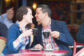 Couple in a Parisian street cafe, drinking coffee — Stock Photo
