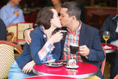 Couple in a Parisian street cafe, kissing — Stock Photo