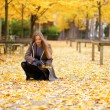 Beautiful girl gathering autumn leaves in park — Stock Photo