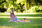 Pretty young girl having a picnic in park — Stock Photo