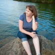 Girl sitting near the lake — Stock Photo