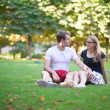 Dating couple sitting on the grass in park — Zdjęcie stockowe