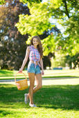 Young girl with basket going to have a picnic — Stock Photo