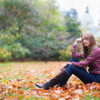 Thoughtful girl sitting on the ground at fall — Stock Photo