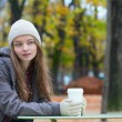 Girl drinking coffee in an outdoor cafe — Stock Photo