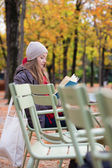 Girl reading a book in an outdoor cafe — Stock Photo