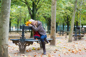 Sad girl sitting on a bench in park — Stock Photo
