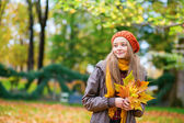 Cheerful young girl with bunch of leaves — Stock Photo