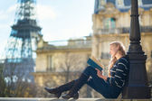 Beautiful young woman in Paris, reading a book — Stock Photo