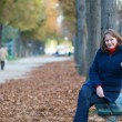 Girl sitting on the bench in park on a fall day — Stock Photo