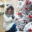 Girl near a Christmas tree covered with snow — Stock Photo