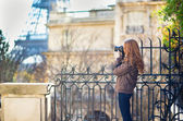 Young girl taking picture of the Eiffel tower — Stock Photo