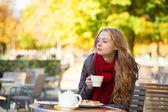 Girl drinking tea in a Parisian cafe — Stock Photo