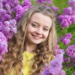 Smiling young girl with lilac blossom — Stock Photo