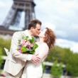 Newlywed couple kissing near Eiffel tower — Stock Photo #37689799