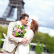 Newlywed couple kissing near Eiffel tower — Stockfoto #37689799