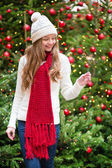 Girl with a sparkler near Christmas tree — Stockfoto