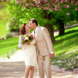 Newlywed couple kissing in park at spring — Stock Photo