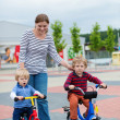 Mother and two sons learning how to ride a bicycle — Stock Photo