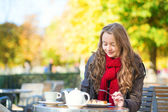 Girl eating waffles in a Parisian outdoor cafe — Foto de Stock