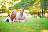 Happy smiling couple lying on the grass — Stock Photo