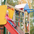Постер, плакат: Little girl preparing to slither from a slide