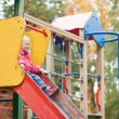 ������, ������: Little girl preparing to slither from a slide