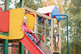 Little girl preparing to slither from a slide — Stock Photo