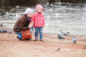 Mother and daughter on beach, looking at birds — Stock Photo