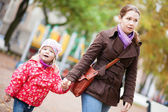 Mother and her daughter walking hand in hand — Stock Photo