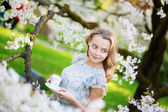 Beautiful woman in cherry garden with cup of tea — Foto de Stock