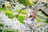 Beautiful woman in cherry garden with cup of tea — Foto Stock