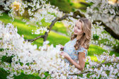 Beautiful woman drinking tea in cherry garden — Stock Photo