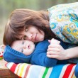 Young mother hugging her 4 month old son — Stock Photo