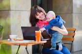 Young mother with little son working on her laptop — Stock Photo
