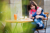 Young mother with her little son having breakfast — Stock Photo