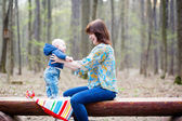 Young mother with her baby in a forest — Stock Photo