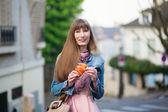 Girl with croissant on a street of Paris — Stock Photo