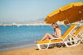 Beautiful girl relaxing on a beach chair — Stock Photo