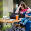 Tired young mother working oh her laptop — Stock Photo #47887391
