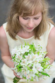 Young bride holding in her hands wedding flowers — Stock Photo