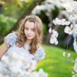Young woman in blooming cherry garden — Stock Photo #47933013