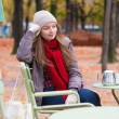 Young girl in an outdoor cafe on a fall day — Stock Photo #48057243