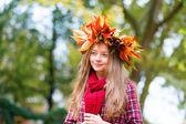 Beautiful girl in colorful autumnal wreath — Stock Photo