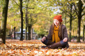 Young beautiful girl sitting on the ground at fall — Stock Photo