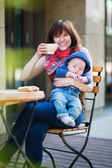 Happy young mother with baby in a cafe — Stock Photo