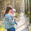 Young mother with her little baby in forest — Stock Photo #48063749