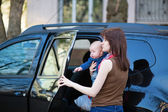 Young mother with her baby getting into a car — Foto de Stock
