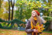 Young girl with bunch of leaves on a fall day — Stock Photo