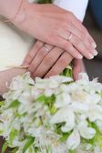 Hands of bride and groom holding wedding bouquet — Stock Photo